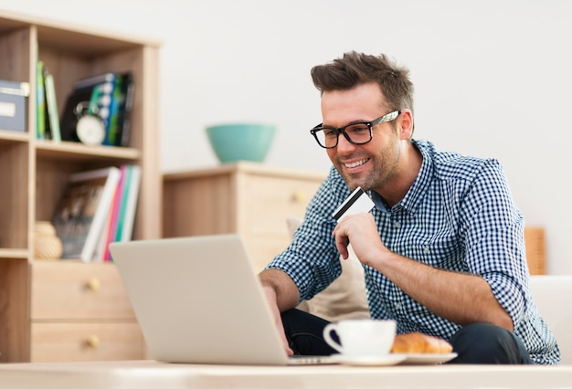 Happy man sitting on sofa with laptop and credit card Free Photo