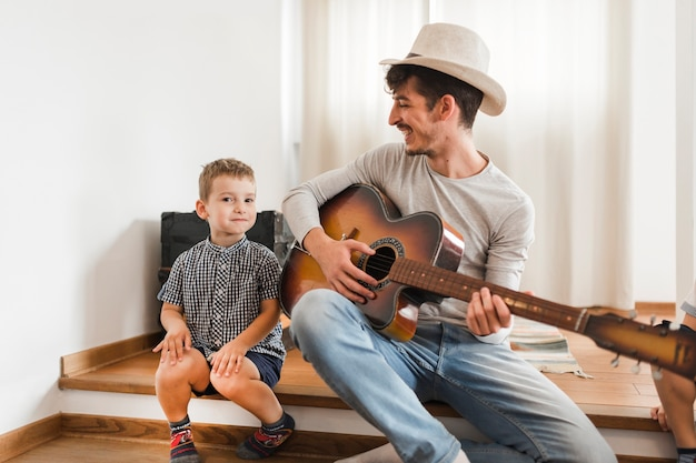 Happy man sitting with his son playing guitar Free Photo