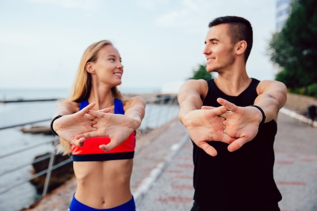 Happy man and smiling woman doing stretching exercises for arms during workout Free Photo
