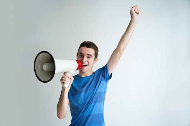 Happy man speaking into megaphone and raising arm Free Photo