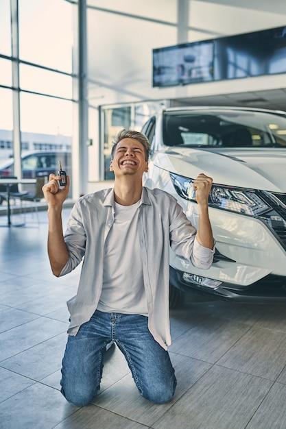 Счастливый человек стоит на коленях, радуясь покупке нового автомобиля в автосалоне Premium Фотографии