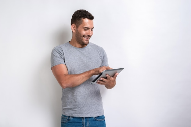 Happy man standing with ipad looking at the screen of it. Premium Photo