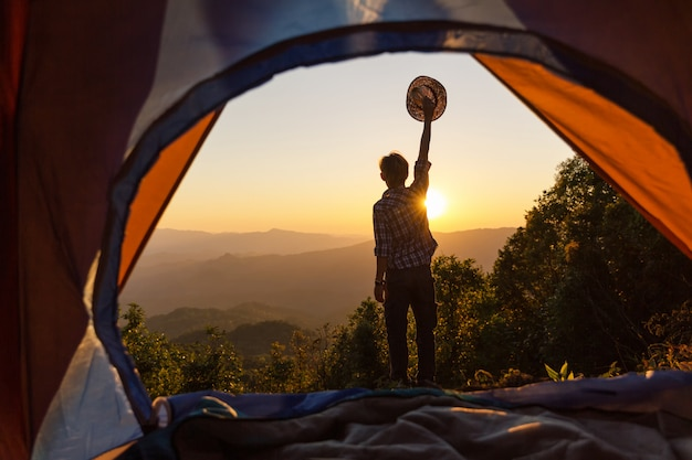 Happy man stay near tent around mountains under sunset light sky enjoying the leisure and freedom. Free Photo