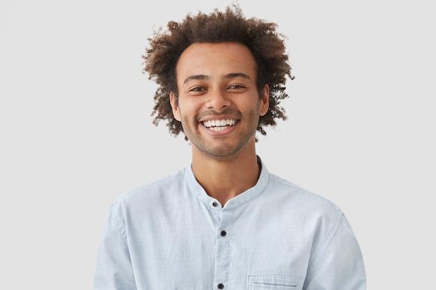Счастливый студент с афро-прической показывает белые зубы в хорошем настроении после уроков Бесплатные Фотографии