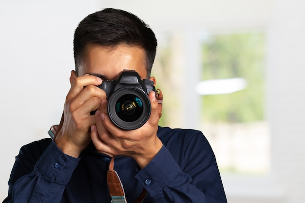 Happy man taking pictures with digital camera Premium Photo