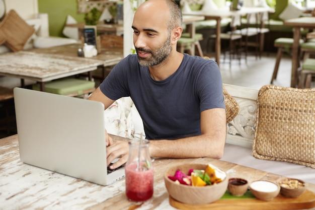 Счастливый человек, набрав сообщение на ноутбуке, имея свежий смузи в ресторане на тротуаре. Бесплатные Фотографии