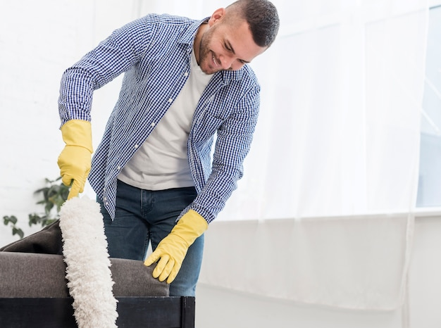 Happy man using a duster Free Photo