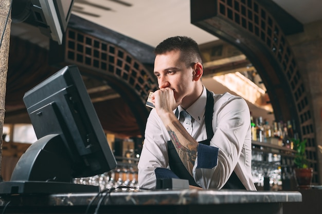 Happy man or waiter in apron at counter with cashbox working at bar or coffee shop Premium Photo