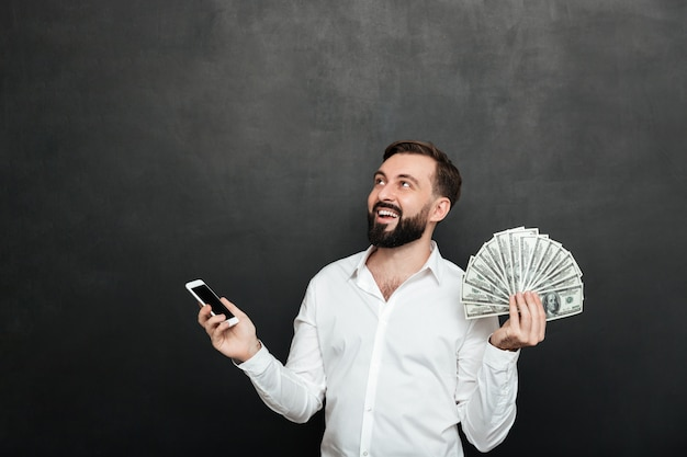Happy man in white shirt winning lots of cash money using his mobile phone, and looking up over dark gray Free Photo