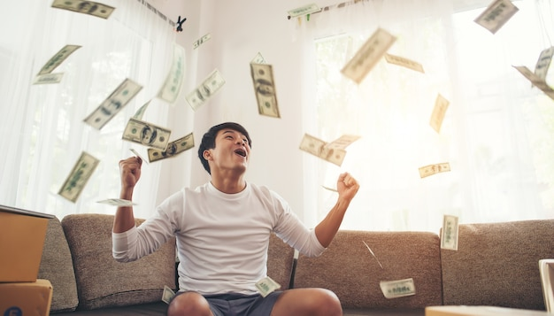 Happy man with cash dollars flying in home office, rich from business online concept