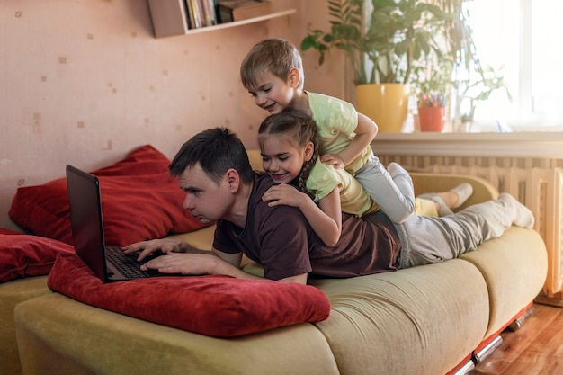 Happy man with children using laptop and earphone during his home working, life in quarantine Premium Photo