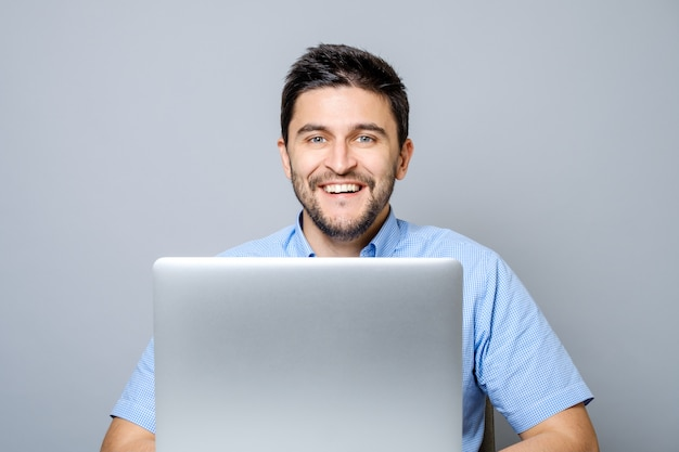 Happy man with laptop computer isolated on gray Premium Photo