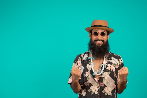 The  of a happy man with a long beard wearing a hat, wearing a striped shirt showing a gesture on a blue . Free Photo