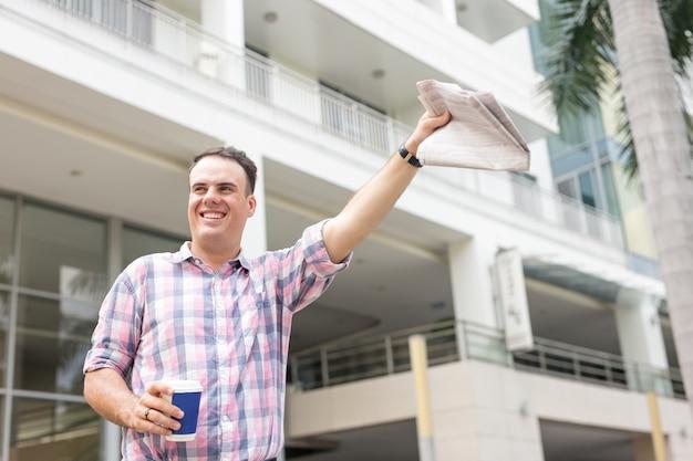 Uomo felice con il giornale hailing taxy on street Foto Gratuite