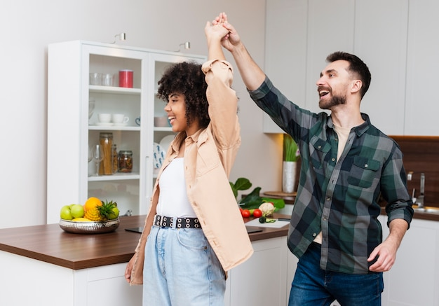 Happy man and woman dancing in kitchen Free Photo