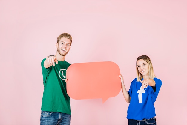 Happy man and woman gesturing while holding empty orange speech bubble Free Photo