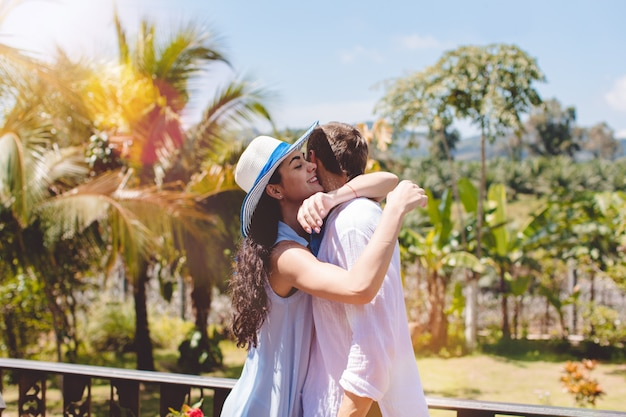 Happy man and woman hugging on terrace or balcony with beautiful tropical landscape young couple in Premium Photo