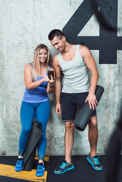 Happy man and woman looking at cellphone in gym Free Photo