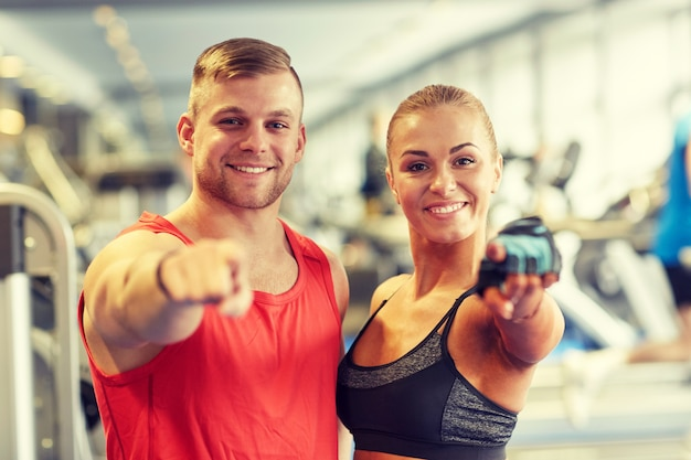 Happy man and woman pointing finger to you in gym Premium Photo