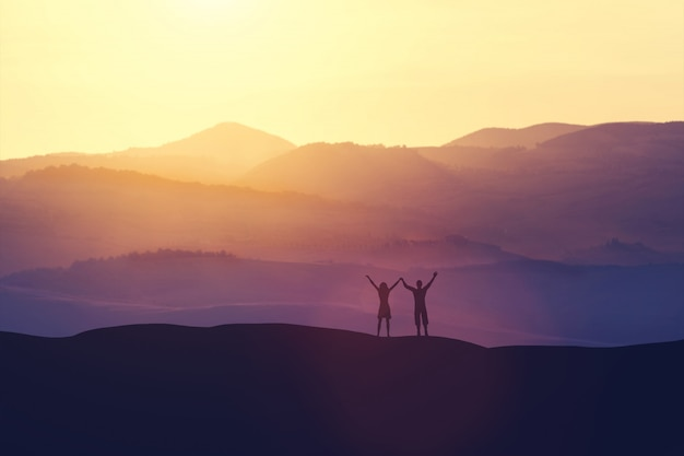 Happy man and woman standing on a hill Premium Photo