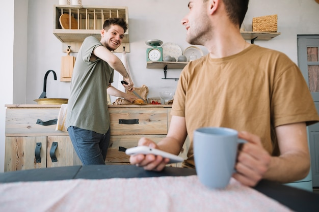 Happy man working in kitchen looking at his friend using mobile phone Free Photo