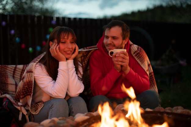Счастливая семейная пара отдыхает у костра и пьет чай на природе Premium Фотографии