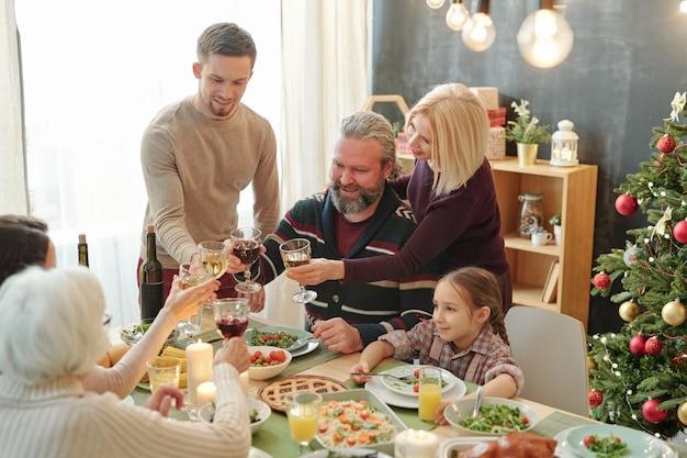 Счастливые зрелые и молодые пары, тосты с бокалами вина за домашней едой на праздничном столе во время рождественского ужина Premium Фотографии