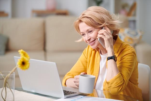 自宅の隔離中にリモートで作業しながらマグカップと携帯電話のクライアントの1つに相談する幸せな成熟した実業家 Premium写真