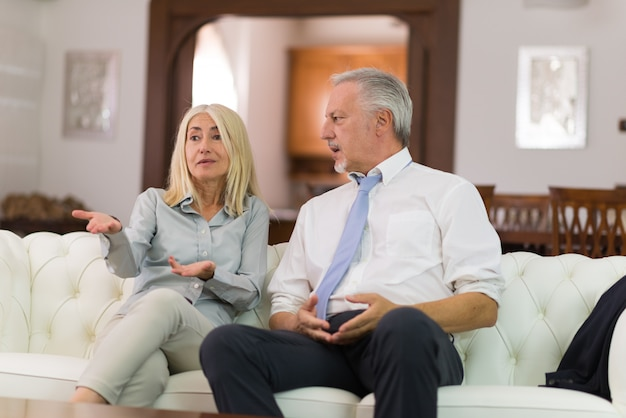 Happy mature couple talking in their home Premium Photo