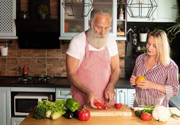 幸せな成熟した愛情のあるカップルの家族がキッチンに立ってサラダを調理します。 Premium写真