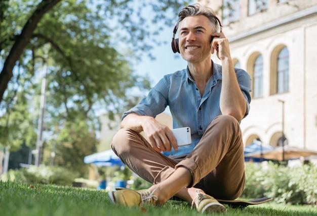 Happy mature man listening to music on headphones, relaxing in park Premium Photo