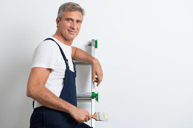 Счастливый зрелый художник, стоя на стремянке, держа кисть Premium Фотографии