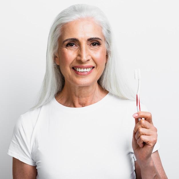 Happy mature woman holding tootbrush Free Photo