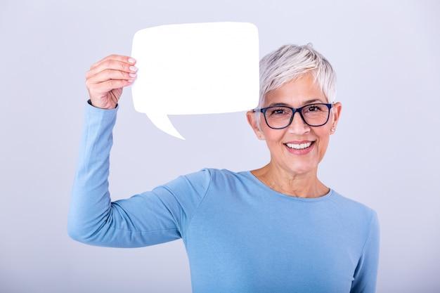 Счастливая зрелая женщина в простой голубой футболке с длинным рукавом держа пустой пузырь речи изолированный на стене. женщина показывает знак речи пузырь, глядя счастливым Premium Фотографии
