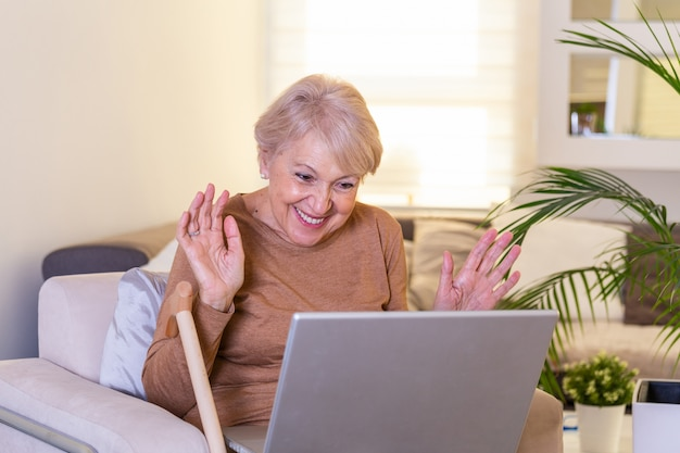 Happy mature woman waving to someone while having a video call over laptop at home. gray-haired senior woman waving hand in front of laptop while having video call with her family members. Premium Photo