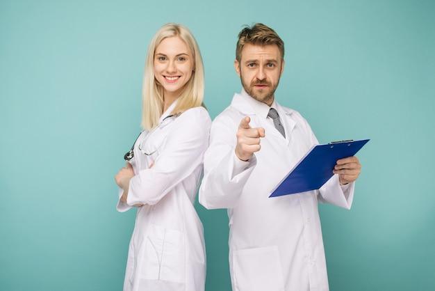 Счастливая медицинская бригада врачей, мужчина, указывающий вперед и улыбающаяся женщина, изолированные над синим пространством Premium Фотографии