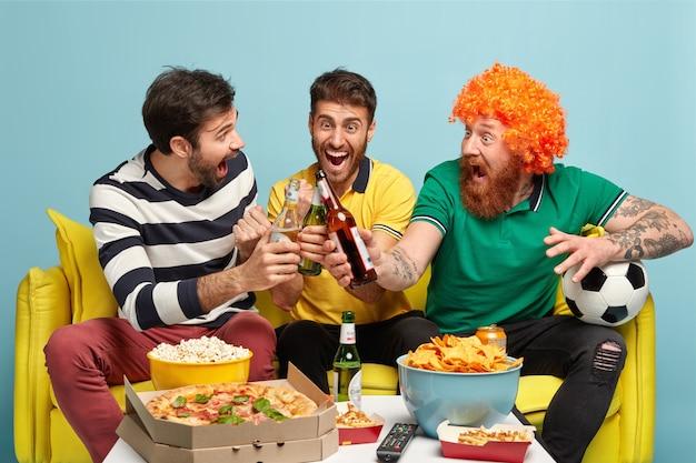 幸せな男性は、彼らがサポートしたサッカーチームの勝利を祝い、ビールのボトルをチリンと鳴らし、家でスポーツトーナメントを見て、軽食をとり、勝利を収めて叫びます。大喜びのファンはテレビで全国大会を楽しんでいます 無料写真