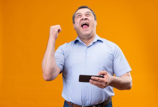 Felice uomo di mezza età che indossa la maglietta blu spogliata, vincendo il gioco sul cellulare e alzando la mano nel gesto di trionfo mentre si trova in piedi Foto Gratuite