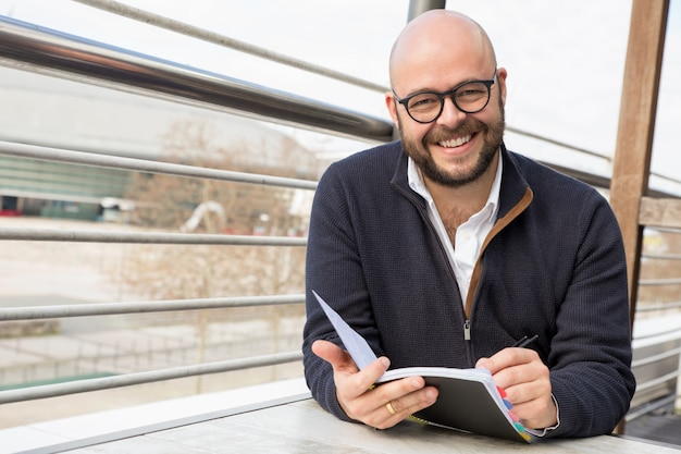 Happy middle-aged man making notes in street cafe Free Photo