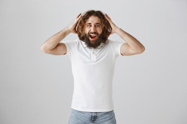 Felice l'uomo barbuto del medio oriente reagisce eccitato alle buone notizie Foto Gratuite