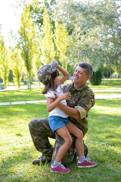ミッション旅行から戻った後、娘を抱き締める幸せな軍の父。お父さんのカモフラージュキャップを試着している女の子。家族の再会または帰国の概念 無料写真