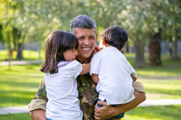 軍のミッション旅行の後に子供たちと会い、子供たちを腕に抱き、笑顔で幸せな軍の父。家族の再会または帰国の概念 無料写真