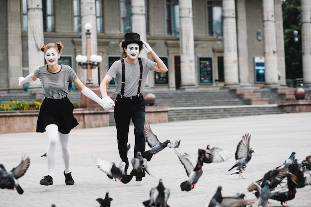 Happy mime couple running near flying pigeons Free Photo