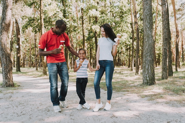 Happy mixed family eating ice cream in forest. Premium Photo