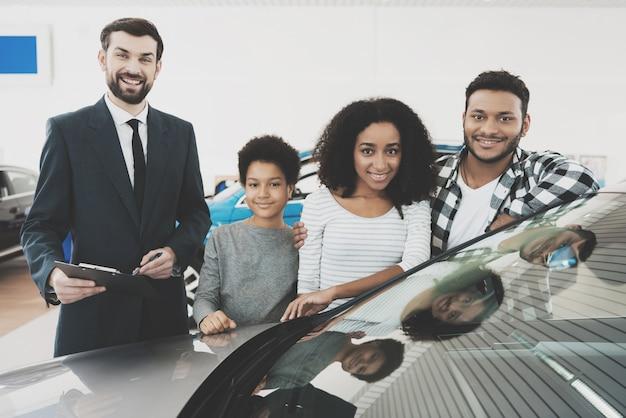 Happy mixed race family and agent near new auto. Premium Photo