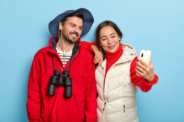 Счастливая смешанная раса прекрасная пара с довольными выражениями лица, делайте селфи на камеру смартфона, вместе проводите отпуск, небрежно одеты, пользуйтесь биноклем Бесплатные Фотографии