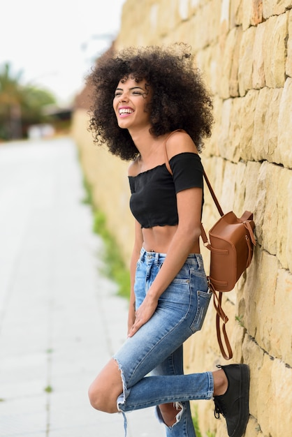 Happy mixed woman with afro hair laughing outdoors Premium Photo