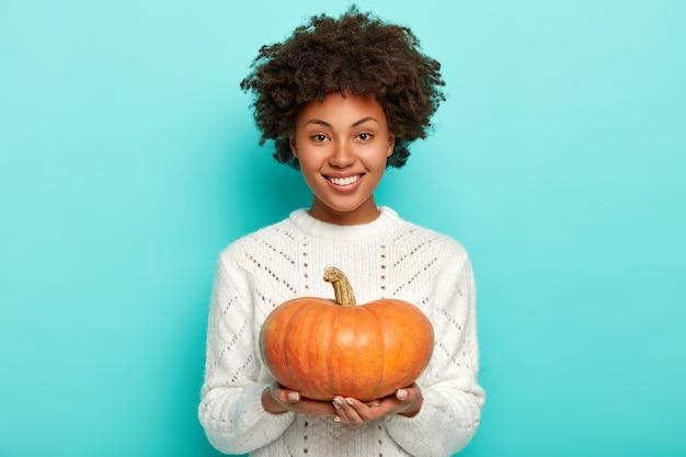 Счастливая модель с волосами афро, держит большую спелую оранжевую тыкву, знает хороший рецепт приготовления вкусной органической еды, носит белый свитер Бесплатные Фотографии
