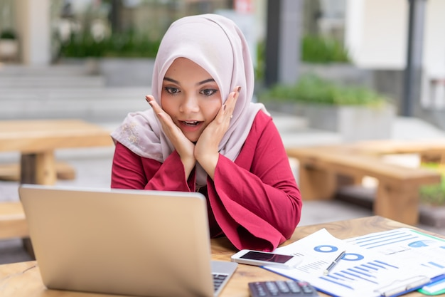 Happy modern asian muslim business woman glad to recieve high profits,has own prosperous business. Premium Photo