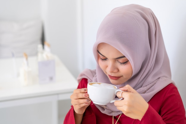 Happy modern asian muslim business woman working on desk smelling coffee. Premium Photo